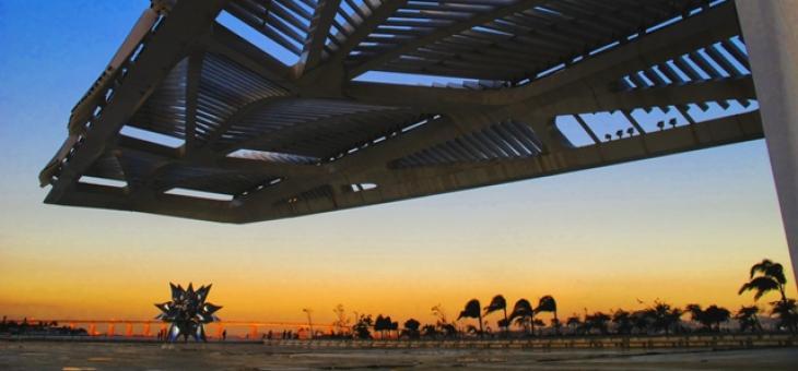 Foto com céu azul alaranjado visto de baixo da marquise do Museu do Amanhã, evidenciando a escultura em forma de pétalas. Ao fundo, coqueiros ao vento e a ponte Rio Niterói iluminada pelo sol