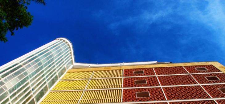 Foto da fachada colorida de tijolos vazados de Edíficio no Parque Guinle, vista de baixo, com o céu azul ao fundo