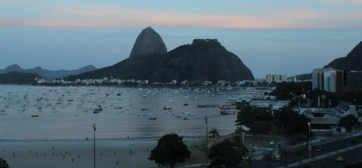 Foto do fim de tarde na enseada de Botafogo, com barquinhos no mar e o Pão de Açúcar ao fundo
