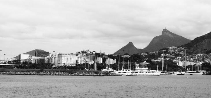 Foto em preto-e-branco da Marina da Glória vista do mar, mostrando alguns barcos e o Corcovado ao fundo