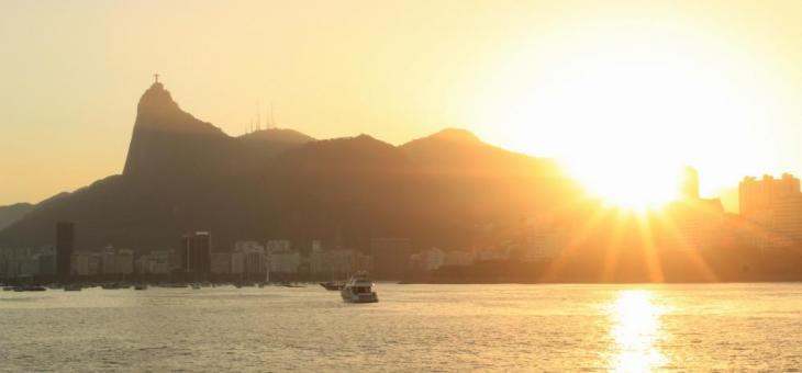 Foto tirada desde o mar, da Baía de Guanabara com os raios amarelos do sol se pondo, os prédios da Praia de Botafogo com o Corcovado ao fundo