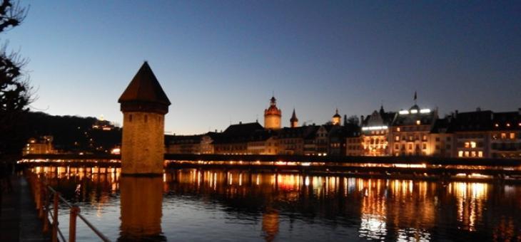 Foto das margens de um rio ao anoitecer, com mureta em primeiro plano e vista de casas coloniais iluminadas. No rio há uma torre.s