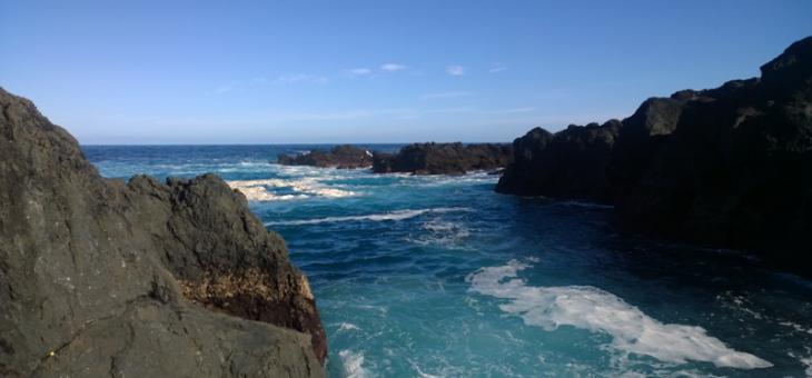 Foto com rochedos do lado esquerdo e direito e no meio o mar que deságua no oceano. Enquanto passa por entre os rochedos, o mar faz pequenas ondas, produzindo um pouco de espuma.