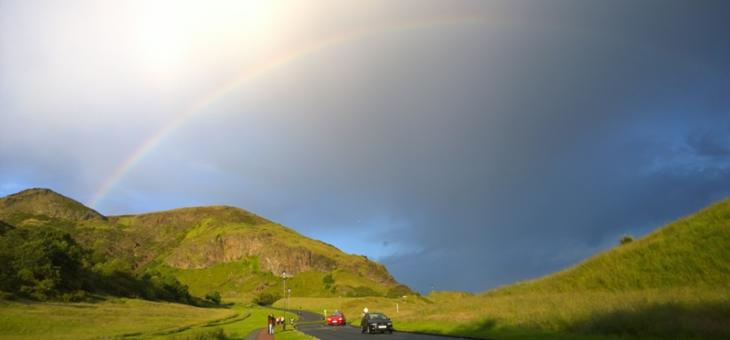 Foto de estrada com entorno e montanhas cobertos de verde, com um caminho onde caminham pessoas e carros passando na estrada. Sol por trás de nuvens carregadas mostrando um arco-íris
