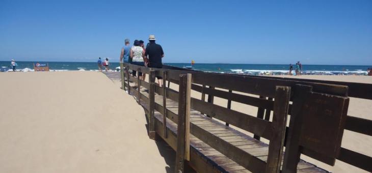 Foto mostra passagem feita de madeira, para viabilizar o acesso, nas areias da Playa Brava, em madeira, com pessoas andando por ela. Ao fundo, a praia.