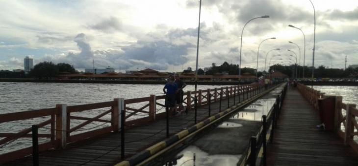 Foto da passarela de acesso ao Trapiche Elizer Levi, onde se vê ao fundo a cidade, e o rio nas laterais