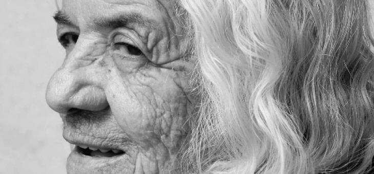 Imagem em preto e branco de uma senhora, do busto para cima, de perfil, com cabelos grisalhos e marcas de expressões nítidas, com um leve sorriso e um olhar distante