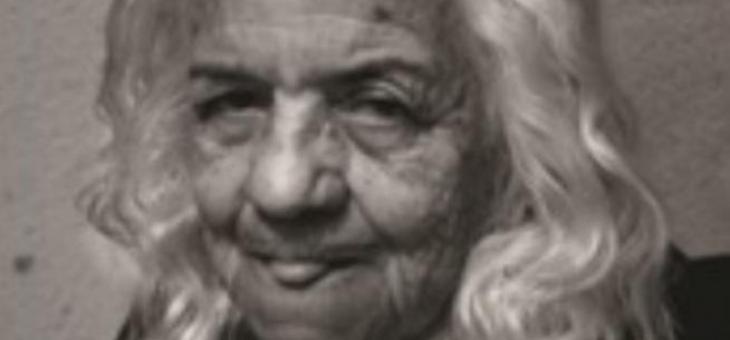 Imagem em preto e branco de uma senhora, do busto para cima, de frente para a câmera, com cabelos grisalhos, marcas de expressões nítidas e mostrando a língua em forma de protesto