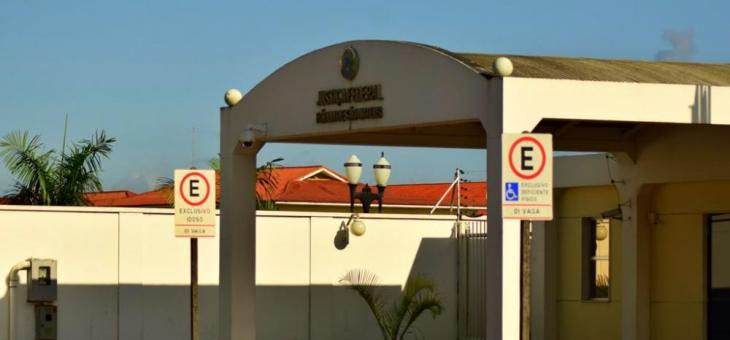 Foto de entrada de foro da Justiça Federal, com placas para estacionamento de idosos e deficientes em primeiro plano
