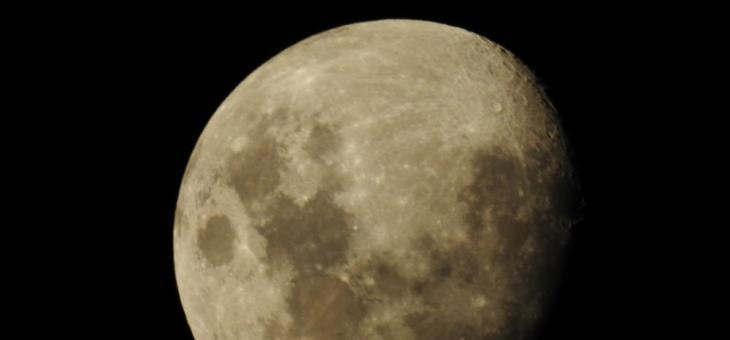 Foto da lua crescente em primeiro plano ocupando quase toda a imagem, com o céu negro ao fundo.