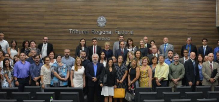 Foto com magistrados e servidores no auditório onde se vê o símbolo do TRF2 ao fundo