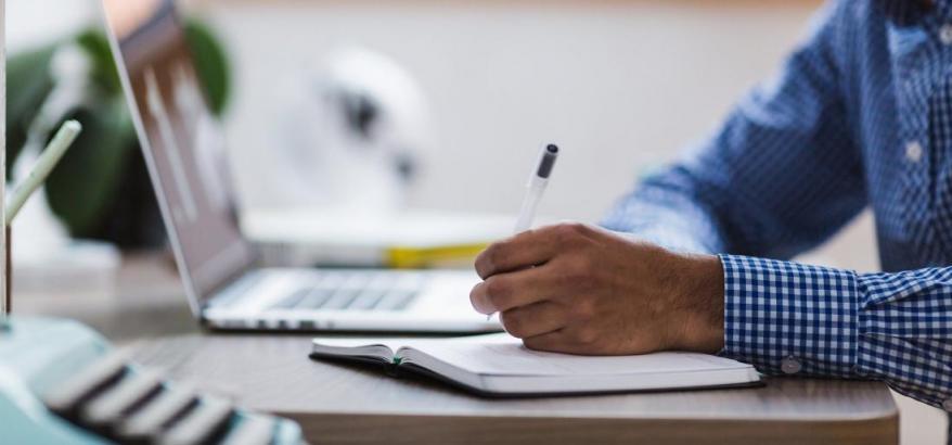 homem escrevendo em uma agenda em frente ao notebook