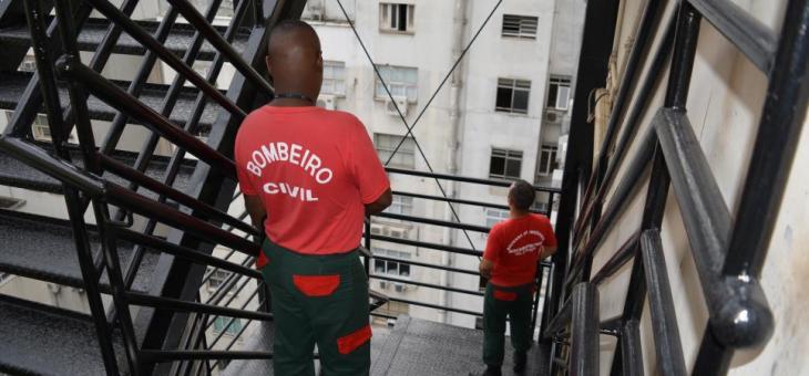 Bombeiros civis observam uma das saídas de emergência do prédio da sede administrativa