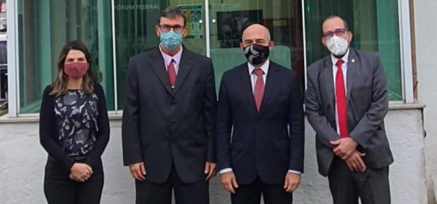 Foto de três juízes e uma juíza de pé, em frente à Seção Judiciária de Resende