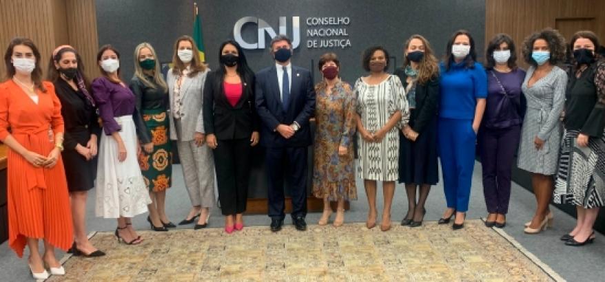 Grupo de treze juízas, de pé, com o Ministro Luiz Fux ao centro, No fundo, logotipo CNJ.