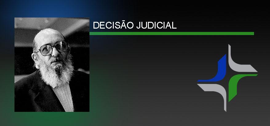 imagem com fundo azul esverdeado, a direita foto de Paulo Freire e a esquerda a logo da justiça federal (em verde, azul e cinza). No centro da imagem, acima, escrito decisão judicial