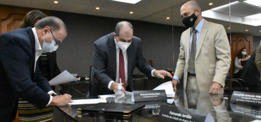 Fernando Jordão e Messod Azulay assinam o termo. À direita, Theophilo Miguel