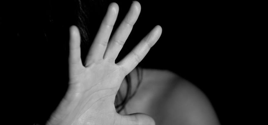 foto em preto e branco de uma mulher com o rosto escondido pela mão com a palma virada pra frente