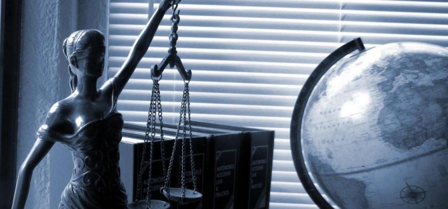 imagem da estatua da justiça junto a livros e um globo terrestre