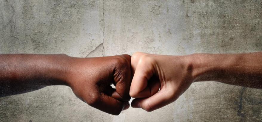 """Imagem de duas mãos em gesto de cumprimento, sendo a de uma pessoa negra e uma branca, com a seguinte legenda, em letras brancas: """"TRF2 realiza audiência pública com poupadores que reclamam expurgos de planos econômicos"""""""