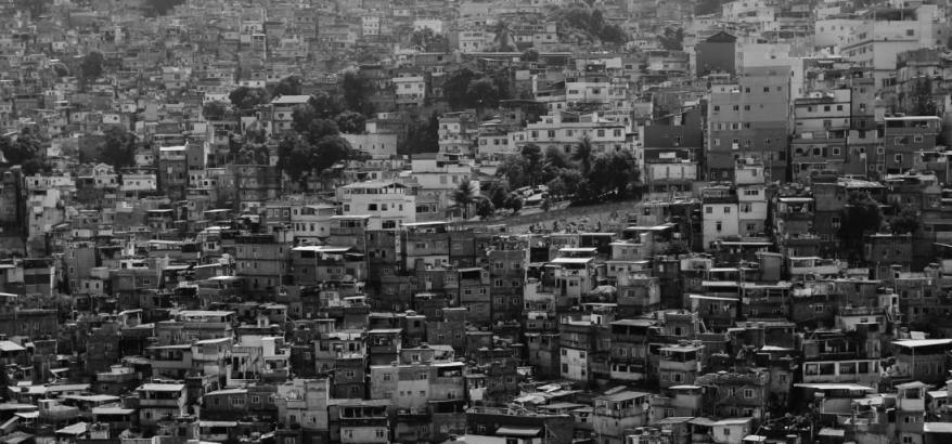 foto em preto e branco de uma favela, com várias casas grudadas construídas em um morro