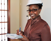 Mulher negra, de blusa marrom e capacete, fazendo anotações