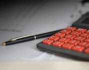 calculadora com teclas vermelhas sobre papéis